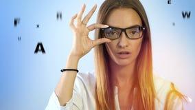 Piękna dziewczyna sprawdza wzrok w oftalmologu z szkłami zdjęcie wideo