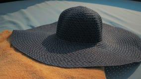 Piękna dziewczyna stawia na błękitnym kapeluszu, kłama na deckchair Lato Sun zbiory wideo