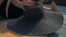 Piękna dziewczyna stawia na błękitnym kapeluszu, kłama na deckchair Lato Sun swobodny ruch zbiory wideo