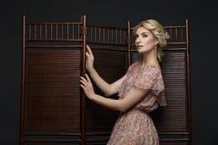 Piękna dziewczyna stoi blisko falcowanie ekranu obrazy stock