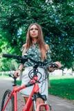 Piękna dziewczyna stoi obok czerwonego bicyklu na tle drzewa w parku W lecie na ?wie?ym powietrzu lifestyle zdjęcia stock