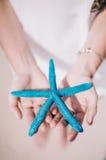 Piękna dziewczyna trzyma błękit pięć wskazuje rozgwiazdy w jego rękach na białej piaskowatej plaży zdjęcia stock