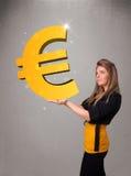 Piękna dziewczyna trzyma dużego 3d euro złocistego znaka Obrazy Royalty Free