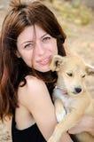 Piękna dziewczyna trzyma małego przybłąkanego psa w jej ar Zdjęcia Stock