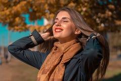 Piękna dziewczyna trzyma ręki włosianego przymknięcie z czerwonymi wargami jego ono przygląda się i ono uśmiecha się Zdjęcia Stock
