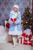 Piękna dziewczyna ubierał w Bożenarodzeniowych charakterach trzyma Nowego Yea Obraz Stock