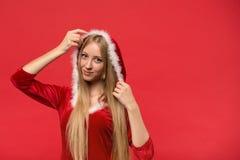 Piękna dziewczyna ubierał w Santa Claus nad czerwonym tłem Zdjęcie Stock