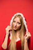 Piękna dziewczyna ubierał w Santa Claus nad czerwonym tłem Obrazy Stock