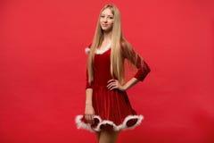 Piękna dziewczyna ubierał w Santa Claus nad czerwonym tłem Zdjęcia Royalty Free
