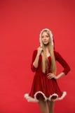 Piękna dziewczyna ubierał w Santa Claus nad czerwonym tłem Obrazy Royalty Free