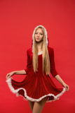 Piękna dziewczyna ubierał w Santa Claus nad czerwonym tłem Zdjęcia Stock