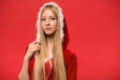 Piękna dziewczyna ubierał w Santa Claus nad czerwonym tłem Obraz Stock