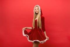 Piękna dziewczyna ubierał w Santa Claus nad czerwonym tłem Fotografia Royalty Free