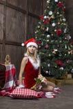 Piękna dziewczyna ubierał w Santa kostiumu blisko choinki Zdjęcie Royalty Free