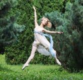 Piękna dziewczyna ubierał w tuniki doskakiwaniu w lato parku Zdjęcie Stock