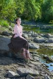 Piękna dziewczyna ubierająca w Boho stylu, siedzi na skale rive Obrazy Stock