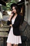 Piękna dziewczyna ubierająca w eleganckiej biel sukni, czarnej kurtce i czarnym kapeluszu, stoi blisko marmurowego stolik do kawy zdjęcia royalty free