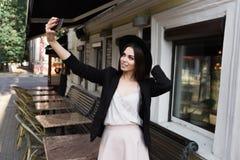 Piękna dziewczyna ubierająca w eleganckiej biel sukni, czarnej kurtce i czarnym kapeluszu, stoi blisko marmurowego stolik do kawy obraz stock
