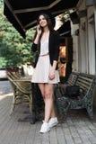 Piękna dziewczyna ubierająca w eleganckiej biel sukni, czarnej kurtce i czarnym kapeluszu, stoi blisko marmurowego stolik do kawy obrazy stock