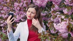 Piękna dziewczyna wśród czereśniowego okwitnięcia Sakura wiosny drzewnych menchii kwitnie robić selfie zbiory wideo