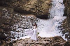 Piękna dziewczyna w ślubnej sukni z bukietem kwiaty na tle lodowiec i góry Obrazy Stock