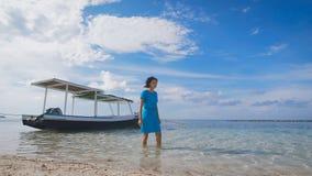 Piękna dziewczyna w błękit sukni odprowadzeniu na wodzie blisko cumować łodzi Szczupła brunetka chodzi blisko do piaskowatej plaż zbiory