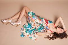 Piękna dziewczyna w barwionym smokingowym lying on the beach na podłoga zdjęcia royalty free