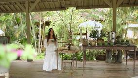 Piękna dziewczyna w biały smokingowy odpoczywać na tarasie i pić herbaty lub kawy Na tarasie tam jest obfitość vegetat zbiory