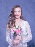 Piękna dziewczyna w białym peignoir z bukietem kwiaty Zdjęcia Royalty Free