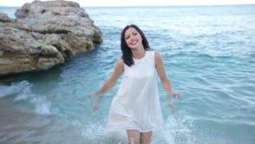 Piękna dziewczyna w biel sukni jest odpoczynkowa na dennego wybrzeża zwolnionym tempie Grecja Pojęcie cudowny lato zbiory