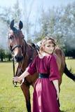 Piękna dziewczyna w Burgundy sukni trzyma brown konia zdjęcia stock