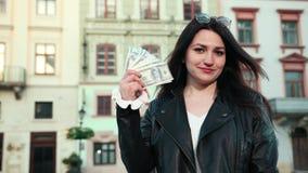Piękna dziewczyna w czarnych szkłach na jej czole podnosi wiązkę dolary i one tworzy wiatr z zadowolonym zbiory