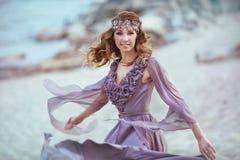 Piękna dziewczyna w czarodziejskiego światła sukni na wybrzeżu Zdjęcia Royalty Free