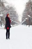 Piękna dziewczyna w czerń uśmiechach przy zimą i stojakach Obrazy Royalty Free