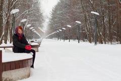 Piękna dziewczyna w czerni siedzi na ławce plenerowej przy zimą Fotografia Royalty Free