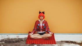 Piękna dziewczyna w czerwonego diabła kostiumowym obsiadaniu w joga pozie w oczekiwaniu na Halloween Jest ubranym czerwoną perukę zdjęcia royalty free