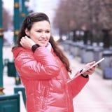 Piękna dziewczyna w czerwonej kurtce z pastylką w parku obraz stock