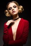 Piękna dziewczyna w czerwonej sukni z głębokim czernią i neckline dzwoni na jego dotyka Model z jaskrawym makeup obraz stock