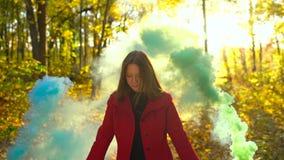 Piękna dziewczyna w czerwoni chwyty barwiącym żakieta dymu w ona ręki i spacery przez żółtego jesień lasu zwolnionego tempa zbiory