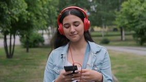 Piękna dziewczyna w czerwonych słuchawkach skacze i słucha muzyki zbiory wideo