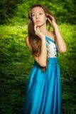 Piękna dziewczyna w długiego błękita smokingowy pozować w lecie Zdjęcia Stock