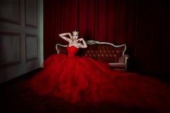 Piękna dziewczyna w długiej czerwieni sukni w królewskiej koronie i Zdjęcia Stock