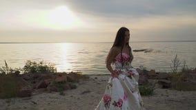 Piękna dziewczyna w długiej pięknej sukni chodzi wzdłuż brzeg rzekiego zbiory