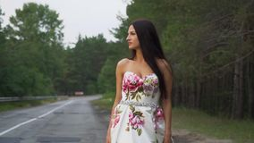 Piękna dziewczyna w długiej sukni chodzi na drodze zdjęcie wideo