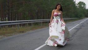 Piękna dziewczyna w długiej sukni wiruje na drodze zbiory wideo