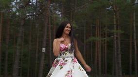 Piękna dziewczyna w długiej sukni wiruje przeciw tłu las zdjęcie wideo