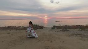 Piękna dziewczyna w długiej wieczór sukni chodzi rzeką Strzelający na trutniu zbiory