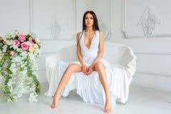 Piękna dziewczyna w długim biel sukni obsiadaniu na leżance obrazy stock