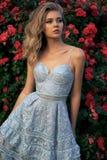 Piękna dziewczyna w eleganckiej sukni pozuje obok róża krzaków Obraz Stock