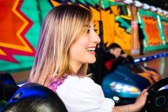 Piękna dziewczyna w elektrycznym rekordowym samochodzie przy parkiem rozrywki obraz stock